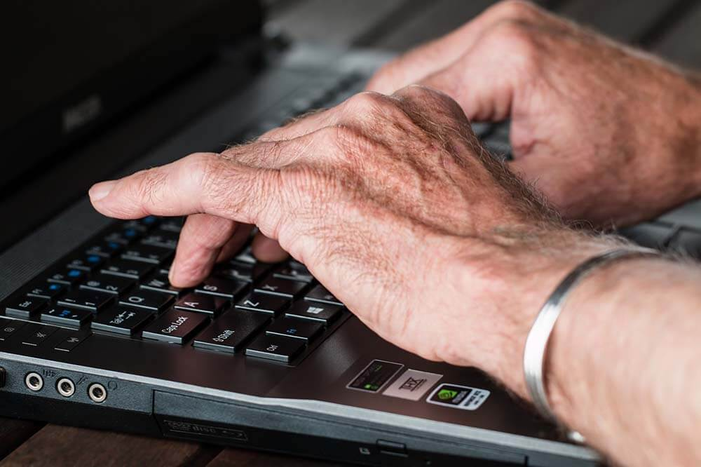 Older adults hands typing on a computer.